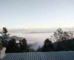Sunrise in the Himalayas seen from the farm. The valley below is covered in fog early morning.